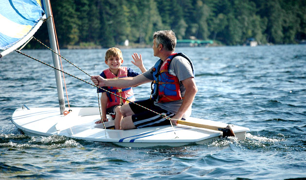 Father and son sail on the winds over Plum Lake